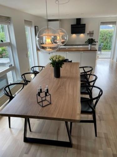 Plank Tisch aus Eiche mit Weißöl, natürlichen Kanten und trapez slim aus schwarzem Metall